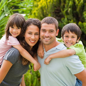Man, woman and two children hugging and smiling outdoors