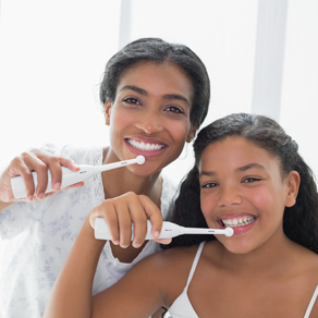 Young girls brushing their teeth and smiling